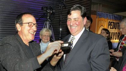 Former city council president Doug Shields, left, shows Councilman Bill Peduto the photo he just took as Mr. Peduto announced his run for mayor of Pittsburgh Thursday at the Crucible Building in the Strip District.