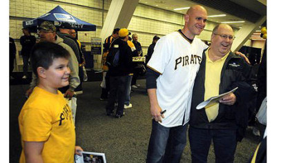 Thomas Nicely, 12, of Delmont, left, watches his father Dennis Nicely get photographed by mom Christine (not in picture) with Pirates shortstop Clint Barmes at PirateFest at David L. Lawrence Convention Center.
