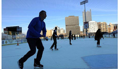 Brian Surmacz of the South Side takes a lap around the newly opened Penguins Pond at the Highmark Stadium in the South Side on Friday.
