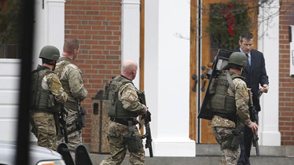 A Conn. State Police tactical team searches the area around Saint Rose of Lima Catholic Church after a scare during services Sunday.
