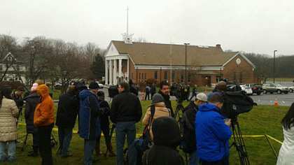 People gather outside Saint Rose of Lima Roman Catholic Church after those attending the noon mass were evacuated.