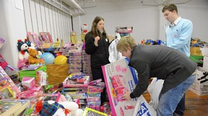 Volunteers, from left, Jayna Walters, 26, of Dormont, Brendan Orient, 23, of Mt. Lebanon and Alex Dziamniski, 23, of Whitehall sort toys Friday at the Toys for Tots open house in the Strip District.