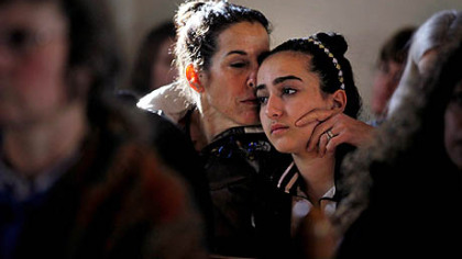 Elizabeth Bogdanoff, left, kisses her daughter Julia, 13, both of Newtown, Conn., during a prayer service Saturday at St. John's Episcopal Church in Newtown.