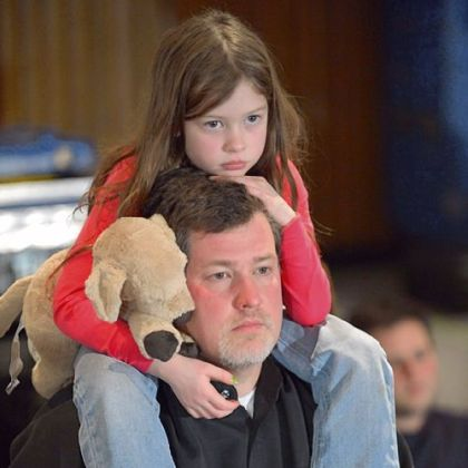 A man and his daughter arrive at Sunday evening's memorial service in Newtown, Conn.