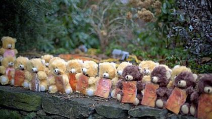 Teddy bears, each representing a victim of the Sandy Hook Elementary School shooting, sit on a wall at a sidewalk memorial Newtown, Conn.