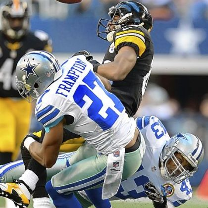The Cowboys' (43) Gerald Sensabaugh separates the ball from Steelers receiver Emmanuel Sanders Sunday at Cowboys Stadium in Arlington, Texas.