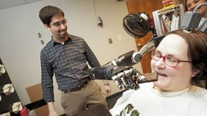 Jan Scheuermann, who has quadriplegia, takes a bite from a chocolate bar she has guided into her mouth with a thought-controlled robot arm. Research assistants Brian Wodlinger and Dr. Elke Brown watch.
