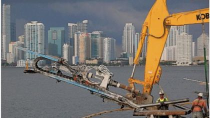 The Miami skyline frames construction crews and equipment at work on the 7-foot wharf expansion necessitated by the deepening of the Panama Canal.