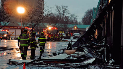 Firefighters look at the burned-out rubble of the Heights Plaza Tuesday in Harrison.