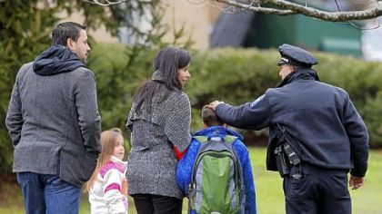Easton, Conn., police officer J. Sollazzo greets a returning student Tuesday as he is walked into Hawley School in Newtown.