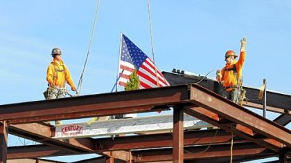 Jason Shipely, left, and Scott Clark of Century Steel Erectors install the last beam during the topping out ceremony Friday at the construction site of the new Cardinal Wuerl North Catholic High School in Cranberry.