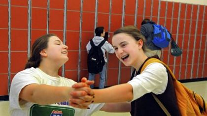 Eighth-graders Caroline Poeggel and Beth Fleming laugh as they dance through their new band room in the renovated middle school.