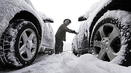 Noah Nichols of Des Moines, Iowa, cleans snow from his car early Thursday. The first widespread snowstorm of the season began a slow crawl across the Midwest with some areas receiving as much as 15 inches.