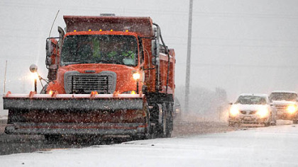 A snow plow spreads salt and sand yesterday near Omaha, Neb. A storm that has dumped more than a foot of snow in the Rocky Mountains is heading east and will begin to impact the Pittsburgh region by Friday.