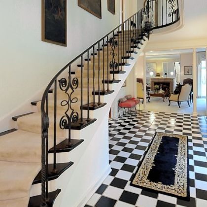 The foyer has a black-and-white checkerboard tile floor and winding staircase.