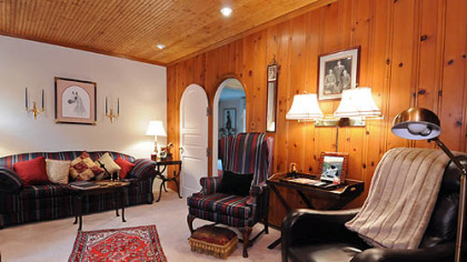 The 16- by 11-foot den has an arched doorway and tongue-and-groove, knotty-pine paneling on three walls and the ceiling.
