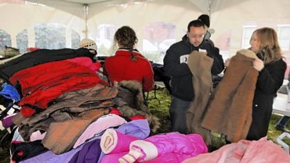 "In the ""Coat Tent,"" Ross Flynn and his mother, Nancy Flynn, sort coats Friday at the Light of Life Rescue Mission on the North Side. The group of volunteers also delivered hot meals to residents in 16 local high-rises and group homes."