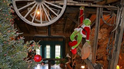 Each Christmas, the Grinch is put into a new spot in Marie and Ron Songer's Christmas display in their sunken living room. Here the Grinch hangs from the bottom of a large wooden antique farm wagon, which is affixed to the ceiling.