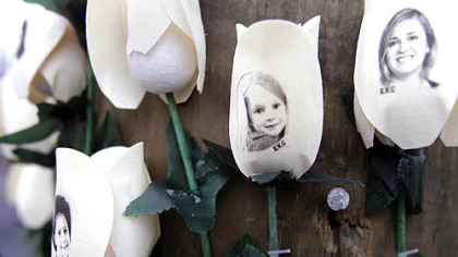 Photos showing those killed in the shootings at Sandy Hook Elementary School are imprinted on faux roses at a memorial Saturday in Newtown, Conn.