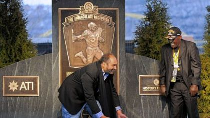 "Franco Harris demonstrates his Immaculate Reception grab as John ""Frenchy"" Fuqua looks on during the unveiling Saturday of a historical marker on West General Robinson Street on the North Shore that designates the exact spot where the play occurred."