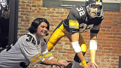 Tess Barker from Iowa City poses for a photograph with the Franco Harris Immaculate Reception statue at the Heinz History Center following today&#039;s session celebrating the 40th anniversary of the event.