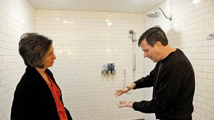 Neil Alexander and his wife, Suzanne, talk in the bathroom attached to the newly renovated master suite in their house in O&#039;Hara. Neil, who was diagnosed with amyotrophic lateral sclerosis in 2011, says that while he can drive just fine, holding a bar of soap is difficult. One feature of the wheelchair-accessible bathroom is soap dispensers that bypass the need for Neil to grip a bar of soap.