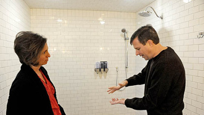 Neil Alexander and his wife, Suzanne, talk in the bathroom attached to the newly renovated master suite in their house in O'Hara. Neil, who was diagnosed with amyotrophic lateral sclerosis in 2011, says that while he can drive just fine, holding a bar of soap is difficult. One feature of the wheelchair-accessible bathroom is soap dispensers that bypass the need for Neil to grip a bar of soap.