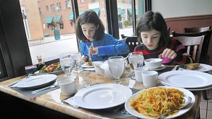 Marissa Alpern, 10, left, and Sylvia Alpern, 8, of Mt. Lebanon have lunch with their parents Tuesday at the China Palace on Walnut Street in Shadyside.
