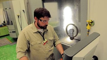 Ben Brewster, a toolmaker from Butler, cuts a component  for a stamping die within .00005 inch at Oberg Industries.