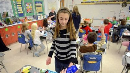 Kaylie Payne, 11, hands out reusable water bottles to a classroom as sixth-graders at South Allegheny Elementary School participate in Project Polar Bear on Friday.  The project advocates the reusable bottles instead of throwaway plastic bottles.