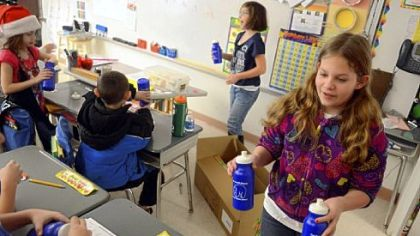 Hayden Bayura, right, 11, hands out reusable water bottles to a classroom.