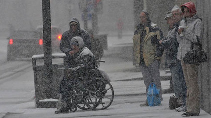 A group of people wait to cross Stanwix Street in Downtown Pittsburgh this morning as heavy snowfall continues.