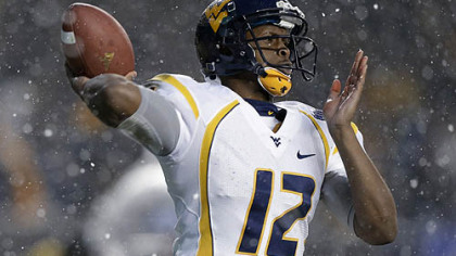 West Virginia quarterback Geno Smith passes in the snow against Syracuse in the second quarter of the Pinstripe Bowl.