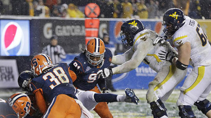 Syracuse defenders bring down West Virginia quarterback Geno Smith for a safety in the first half of the Pinstripe Bowl at Yankee Stadium in New York.