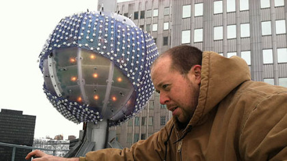 "Rob Gratton, of Integrated Theater Systems, puts the final touches on preparations of ""The Future of Pittsburgh"" ball. It weighs approximately 1,000 pounds and is 6 feet, 7 inches in diameter and will touch a height of 74 feet above the roof of Penn Avenue Place in the 60-second countdown to the New Year of 2013."