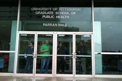 People watch police activity outside a Univeristy of Pittsburgh Graduate School of Public Healtyh building near the shooting scene at Western Psychiatric Institute and Clinic in Oakland this afternoon.