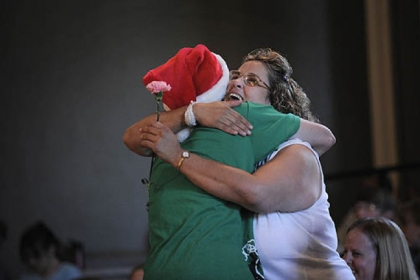 Marion Anderson, 15, of Newport News, Va., hugs Dolores Romanelli Wednesday night after presenting her with a carnation when it was announced that volunteers at the Pittsburgh Project would fix up Ms. Romanelli&#039;s Brighton Heights&#039; home.