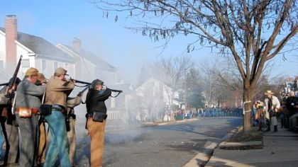 A Confederate unit fires upon advancing Union soldiers on Hanover Street in Fredericksburg, Va. A photographer in period garb, right, sets up to take a picture.