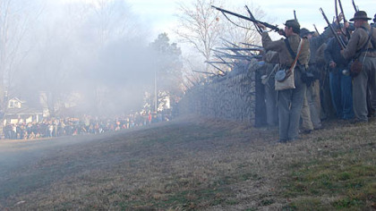 Confederate rifle men fire from behind a replica of the stone wall at the base of Marye&#039;s Heights, where the worst of the fighting occurred Dec 13, 1862, during the Battle of Fredericksburg, Va.