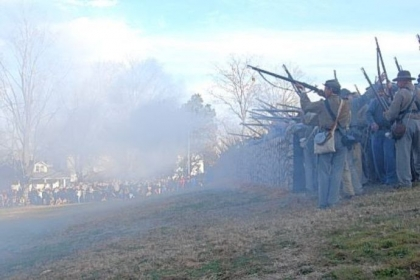 Confederate riflemen fire from behind a replica of the stone wall at the base of Marye's Heights, where the worst of the fighting occurred Dec. 13, 1862, during the Battle of Fredericksburg, Va.